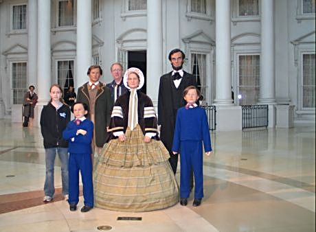 A modern family of dad and daughter pose with the Lincolns at the Abraham Lincoln Museum