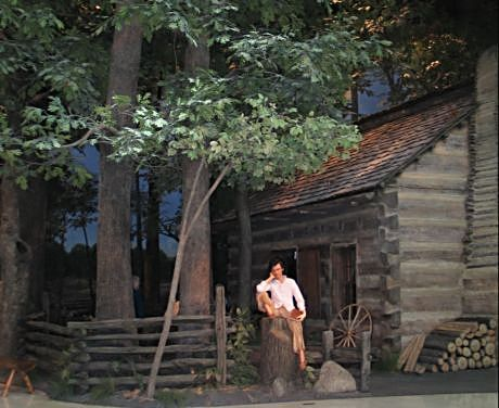A young Abe sits outside his log cabin inside the Abraham Lincoln Museum in Springfield, Ill.