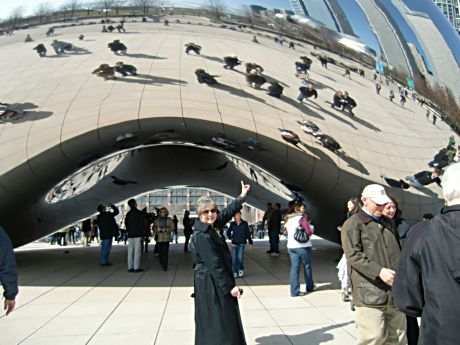 "A tourist notes the ""Bean"" arch and reflections"